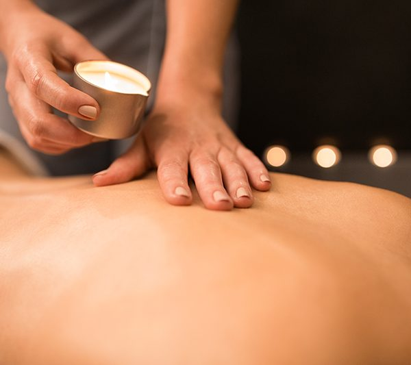 beauty, wellness and bodycare concept - close up of woman having back massage with hot oil candle at spa