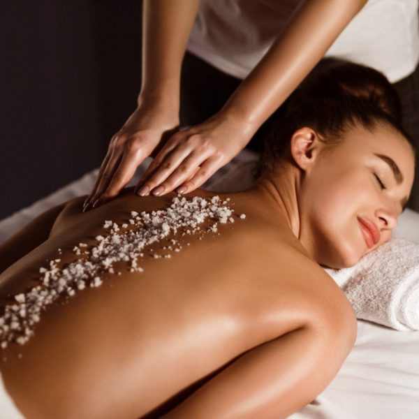 Woman Enjoying Salt Scrub Massage, Relaxing In Health Spa With Closed Eyes