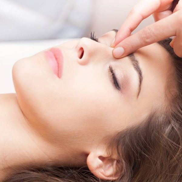 woman acupressure face massage closeup