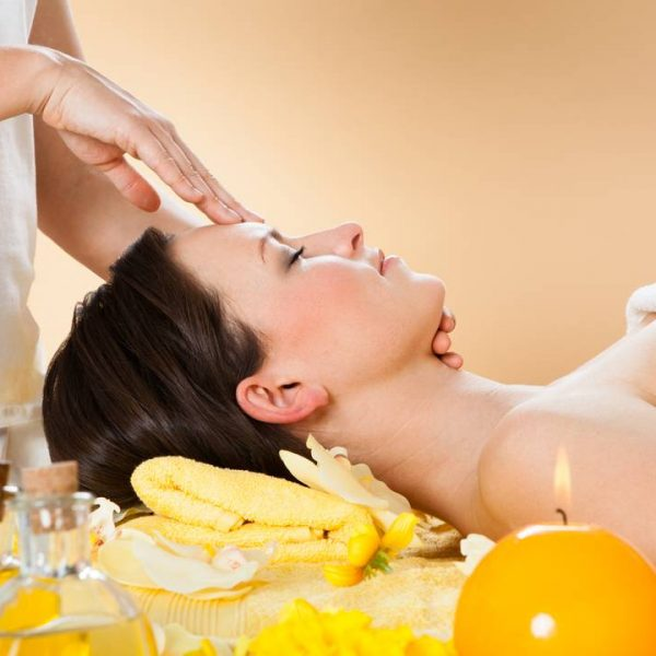 Side view of young woman receiving head massage in spa