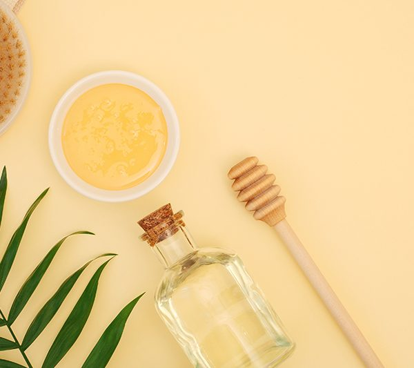 Beautiful background with a set of body skin care cosmetics on a yellow background. Natural honey for massage or mask, brush for dry anti-cellulite massage, sea salt for bath, green leaf, honey dipper