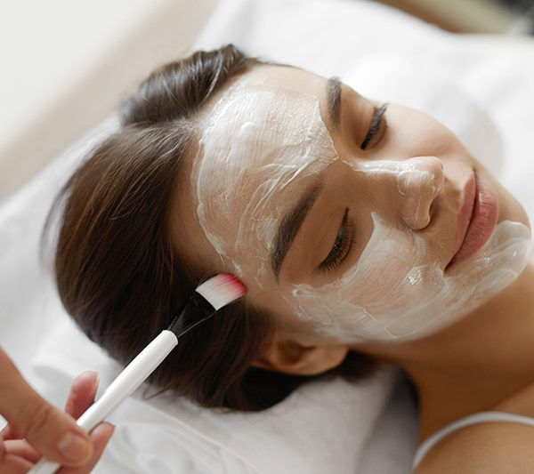 Facial Beauty Treatment. Closeup Of Beautiful Smiling Woman Getting Mask At Spa Salon. Cosmetologist Applying Cosmetic Mask With Brush On Female Face Indoors. Skin Care Concept. High Resolution Image