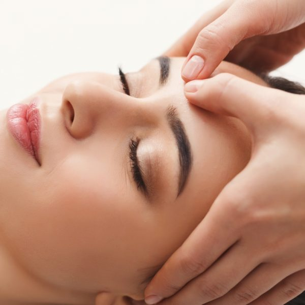 Woman enjoying anti aging facial massage. Pretty girl getting professional skin care at wellness center. Relaxation, beauty, spa and face treatment concept, copy space
